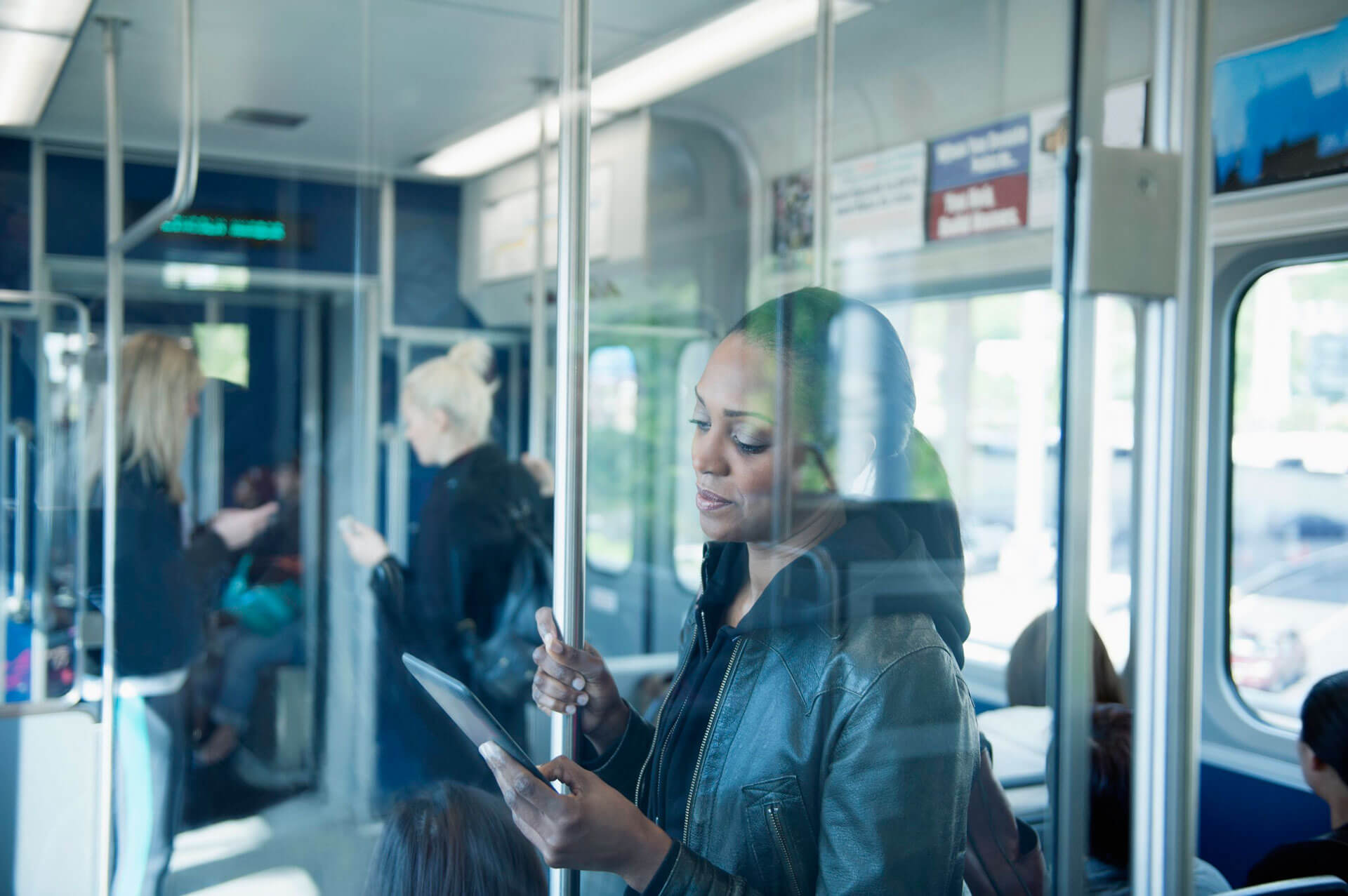 Eine Frau steht in einem öffentlichen Verkehrsmittel und schaut auf ein Tablet. – Bild: GettyImages © Jose Luis Pelaez Inc/Blend Images LLC